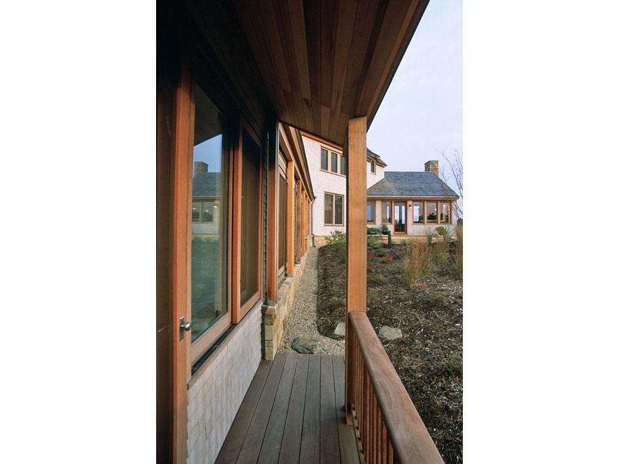 Green home design provides a sheltered porch at the Cape Cod house.