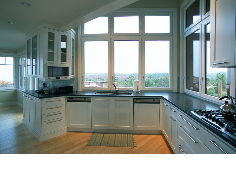 Green home design provides a beautiful view out of the kitchen in the Cape Cod house.