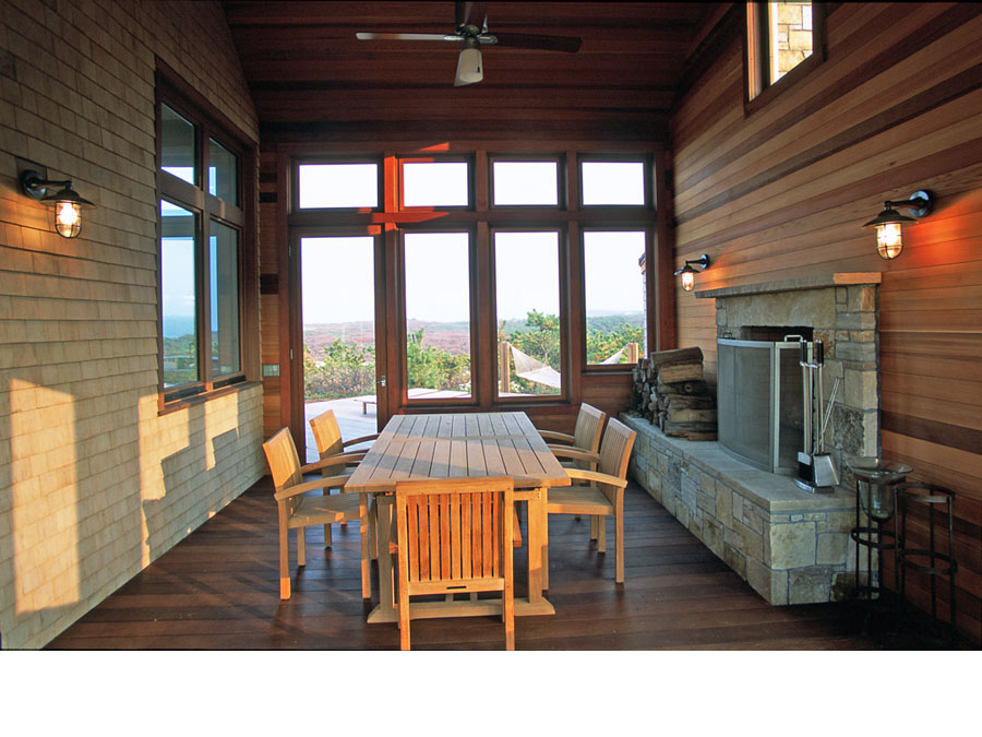Green home design creates a sheltered outdoor living area in the Cape Cod house.