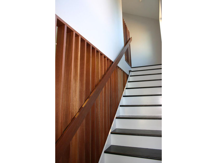 Stairs with a simple railing in the Somerville home renovation.